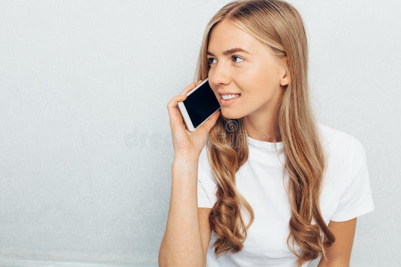 A menina bonita vestiu-se em um t-shirt branco, falando no telefone, em um fundo cinzento fotografia de stock