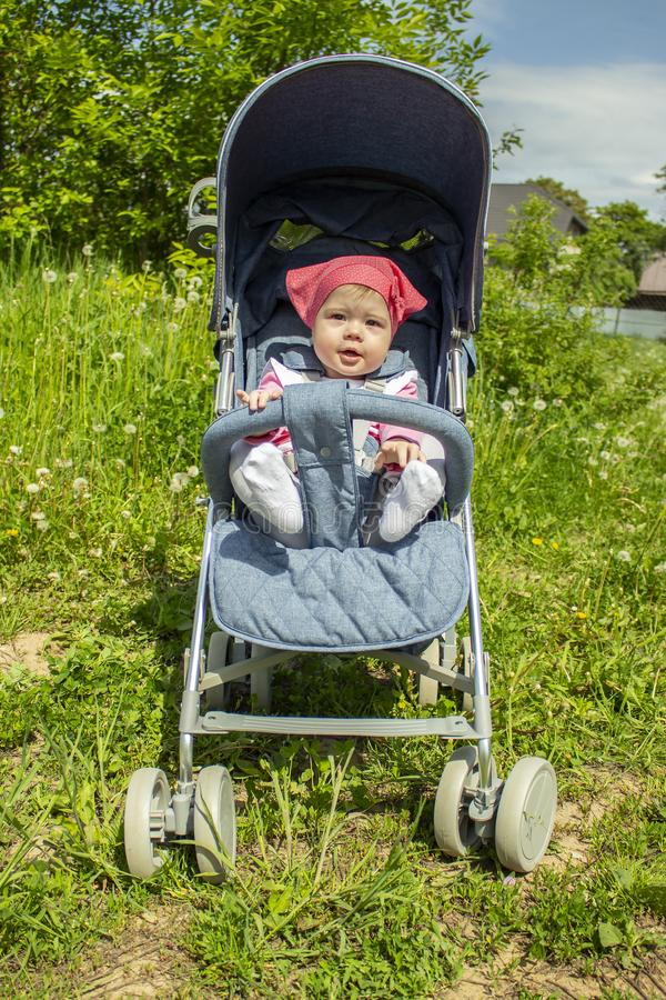 A menina bonito alegre em um lenço cor-de-rosa anda em um carrinho de criança azul Bebê 9 meses de pés que conversam o assento em imagens de stock royalty free