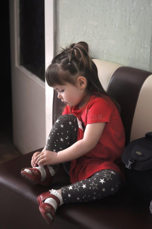 A menina bonito amarra laços em suas sapatas no jardim de infância, escola imagens de stock