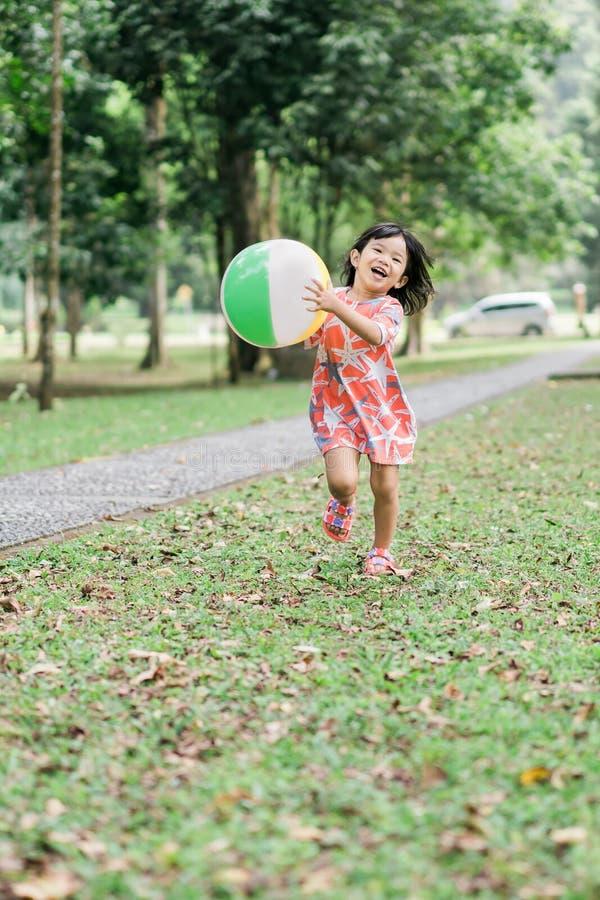 A menina bonito asiática aprecia jogar apenas no jardim foto de stock royalty free
