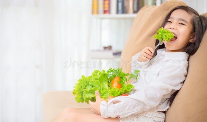 A menina bonito asiática come a salada fresca, conceito saudável comer fotos de stock