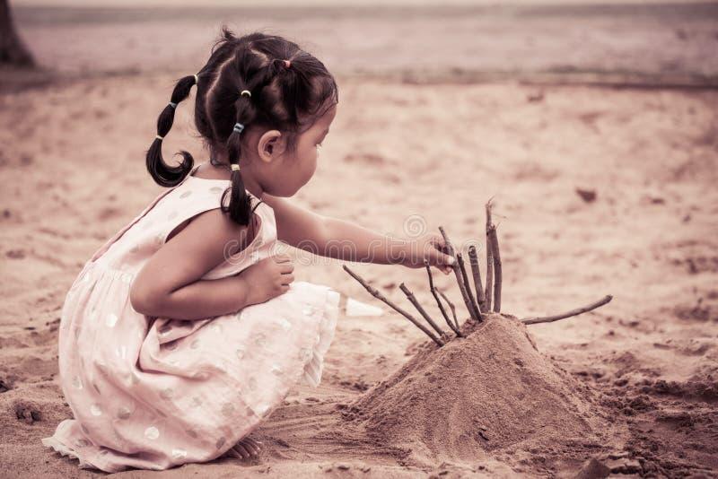 Menina bonito asiática da criança que joga com a areia no campo de jogos imagens de stock royalty free