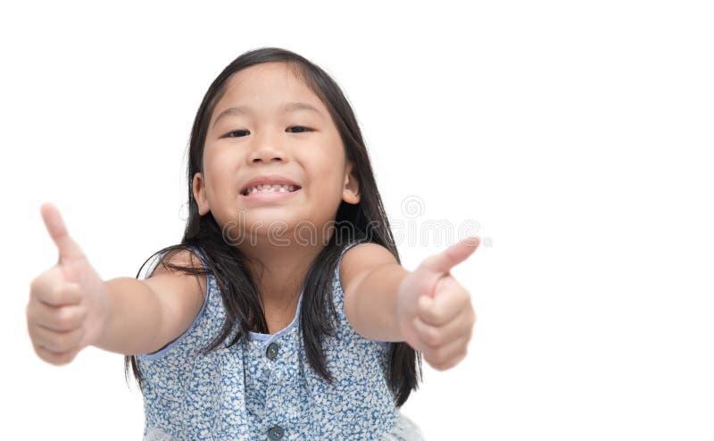 A menina bonito asiática feliz que mostra os polegares levanta o gesto foto de stock royalty free