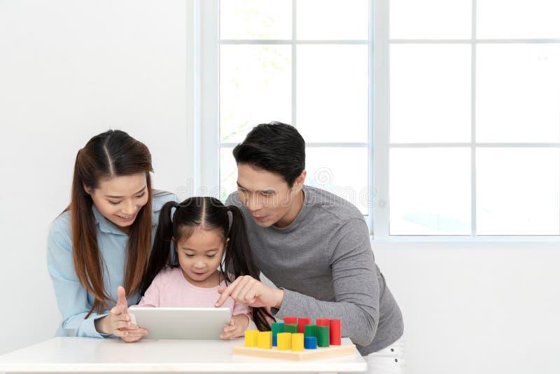 Menina bonito asiática pequena nova feliz que olha ou que joga a tabuleta, o portátil ou o móbil digital com pais alegres na mesa imagem de stock