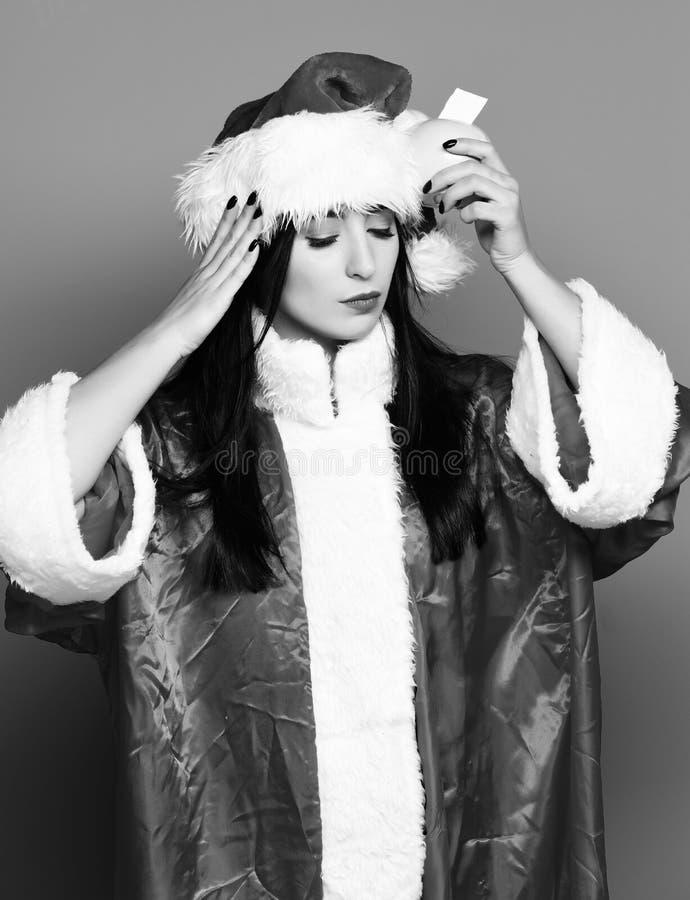 A menina bonito bonita de Santa ou a mulher moreno com os olhos próximos na camiseta do ano novo e no Natal ou no chapéu do xmas  fotografia de stock