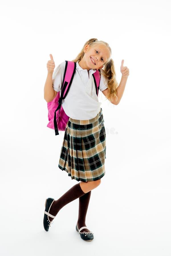 Menina bonito bonita do cabelo louro com um schoolbag cor-de-rosa que olha o polegar da exibição da câmera acima do gesto feliz i fotografia de stock