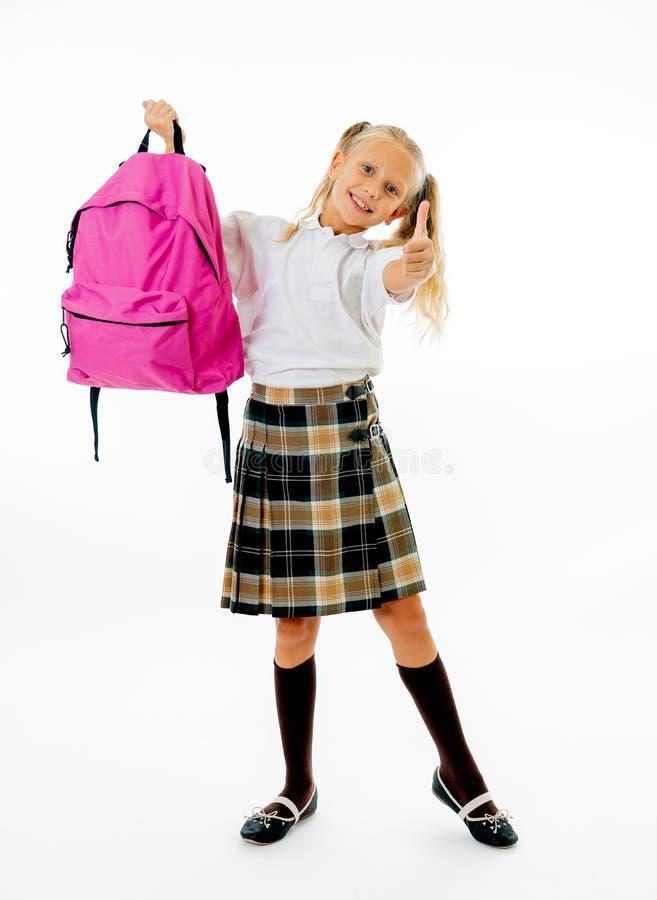 Menina bonito bonita do cabelo louro com um schoolbag cor-de-rosa que olha o polegar da exibição da câmera acima do gesto feliz i fotografia de stock royalty free