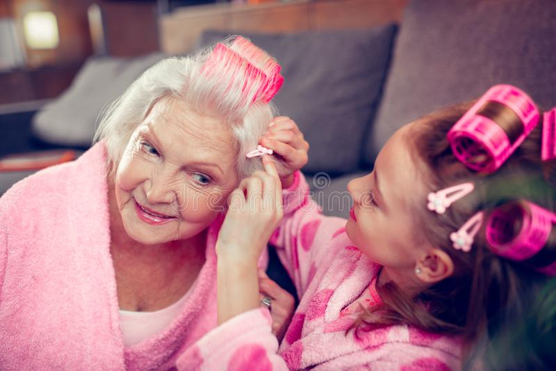 Menina bonito bonita que põe o gancho de cabelo sobre o cabelo de sua avó bonita fotos de stock