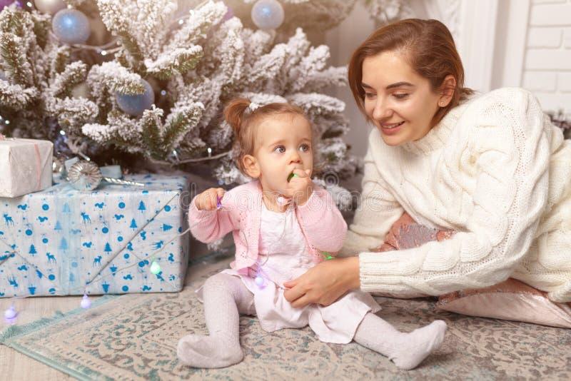 Menina bonito bonita que senta-se no assoalho perto da árvore do ano novo ao lado de sua mãe Humor do feriado, valores familiares imagem de stock royalty free