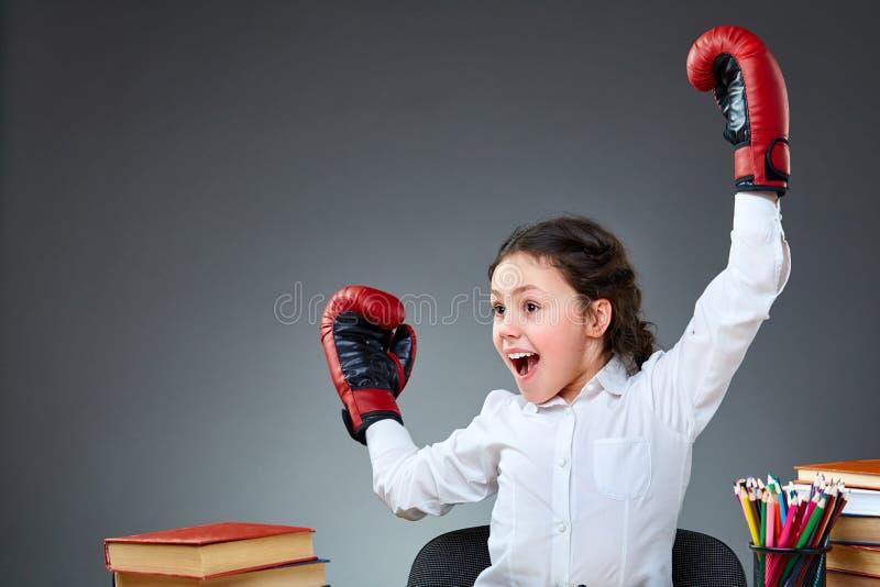Menina bonito brincalhão que tem o divertimento em luvas de encaixotamento ao inclinar-se no fundo cinzento, foco seletivo fotografia de stock
