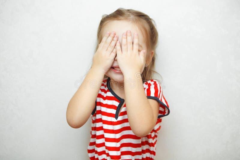 A menina bonito cobre sua cara com as palmas foto de stock royalty free