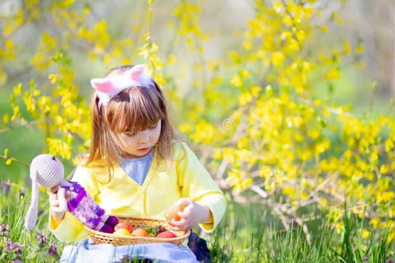 Menina bonito com as orelhas do coelho do cabelo encaracolado e o vestido vestindo do verão que têm o divertimento durante a ca fotografia de stock