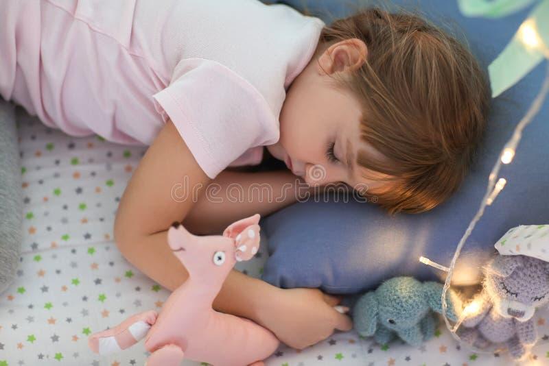 Menina bonito com brinquedos que dorme na barraca do jogo imagens de stock royalty free