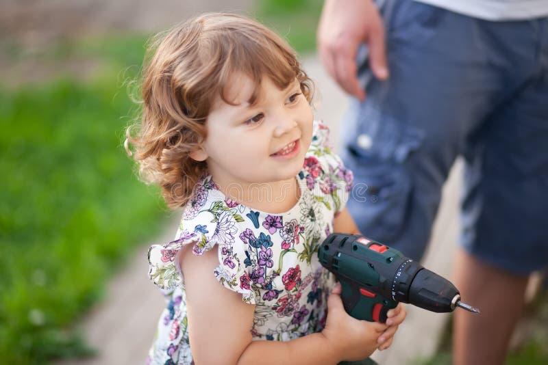 Menina bonito com broca do pai, fora foto de stock