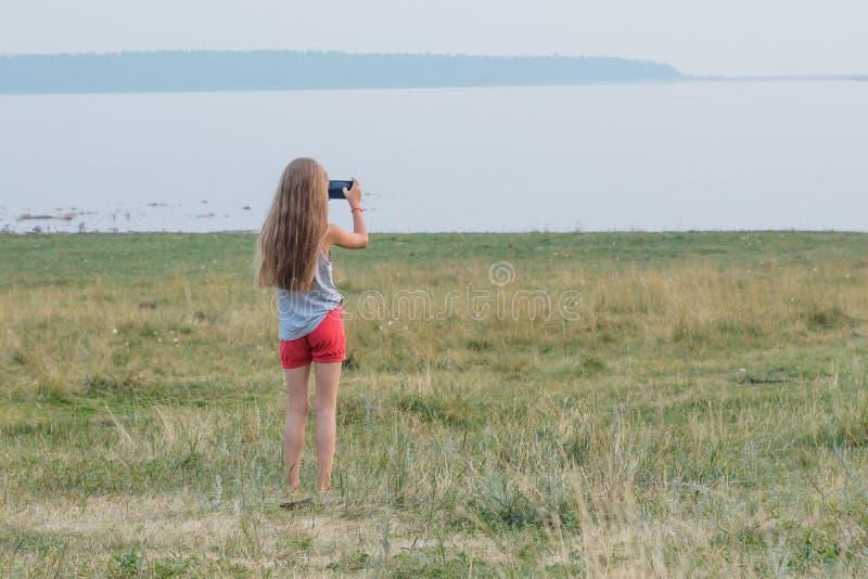 A menina bonito com cabelo louro longo está no lago e toma a imagem da paisagem no smartphone imagem de stock royalty free