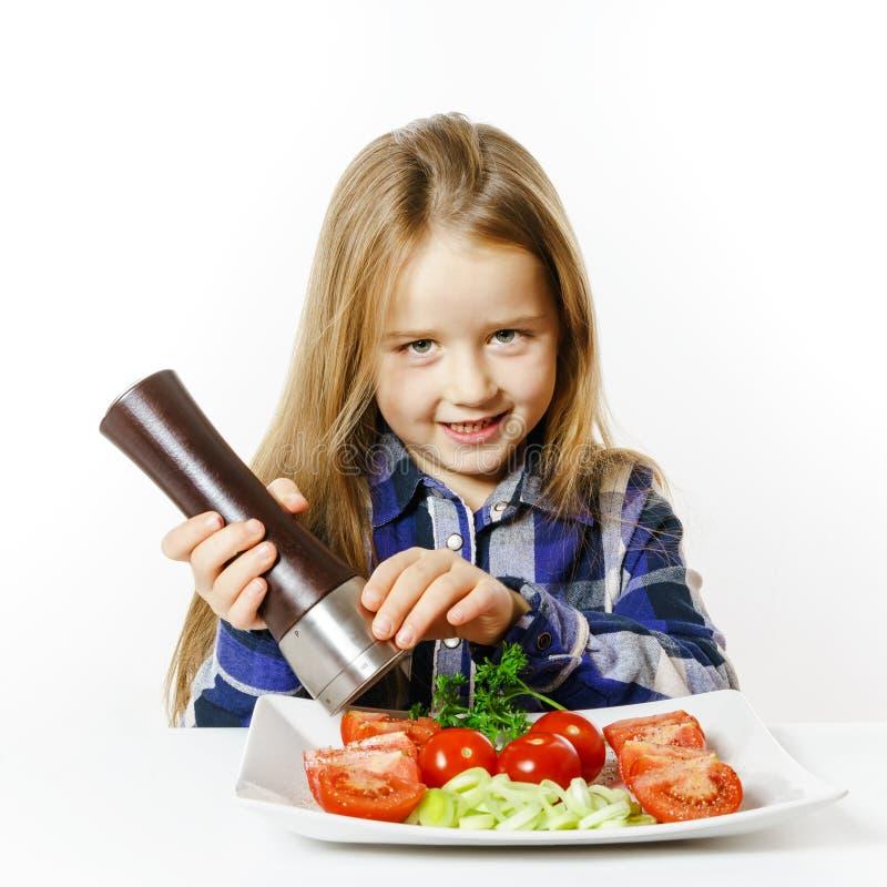 Menina bonito com a caixa da salada e de pimenta foto de stock