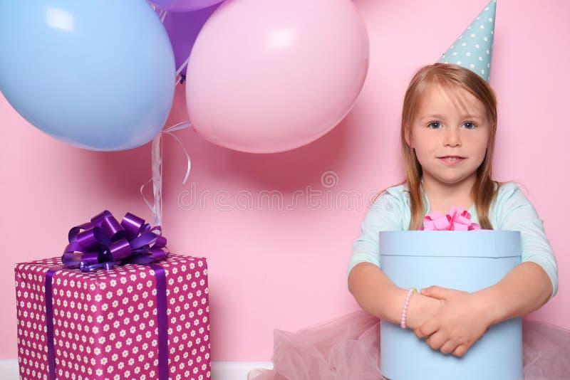 Menina bonito com caixas de presente e balões no fundo da cor Celebra??o do anivers?rio foto de stock