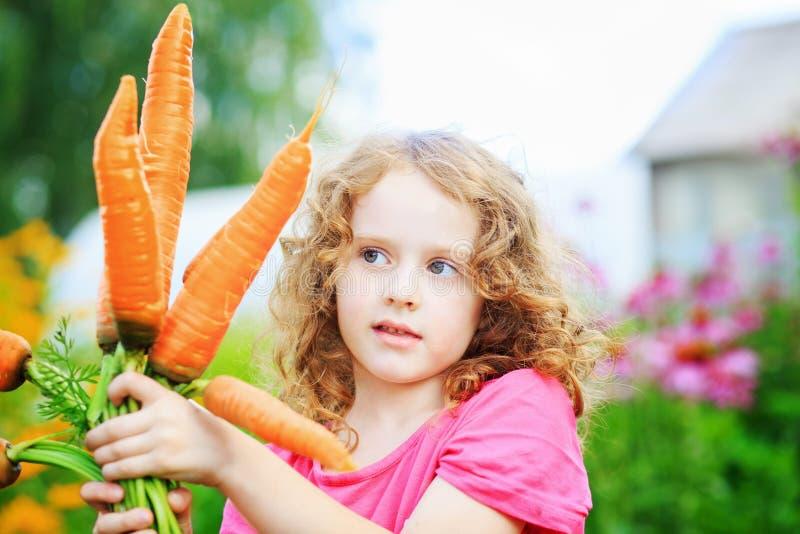 Menina bonito com cenoura amarela foto de stock