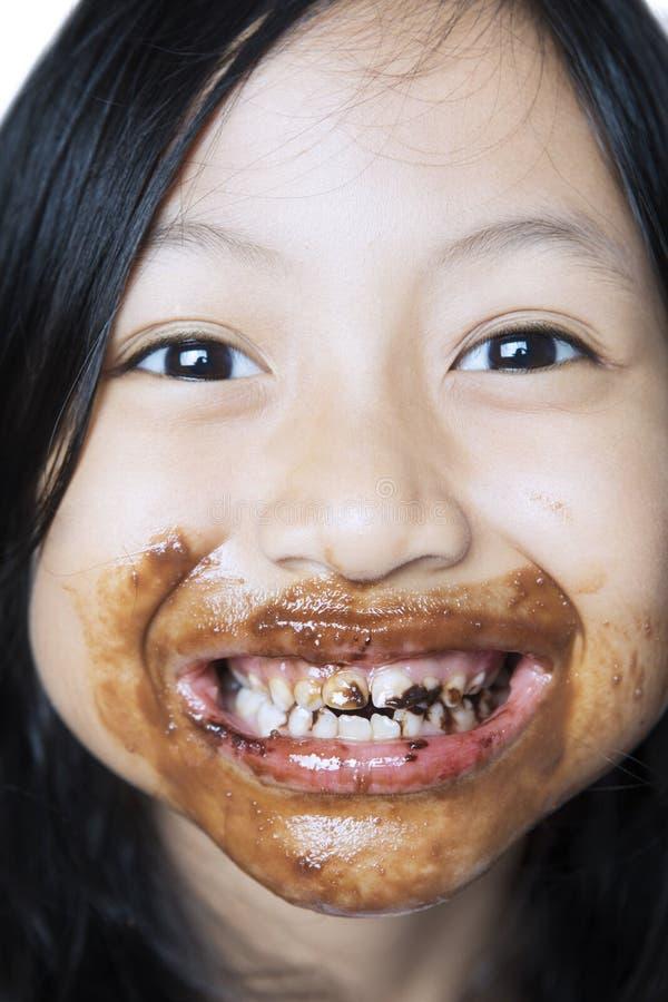 Menina bonito com chocolate em sua boca fotos de stock royalty free