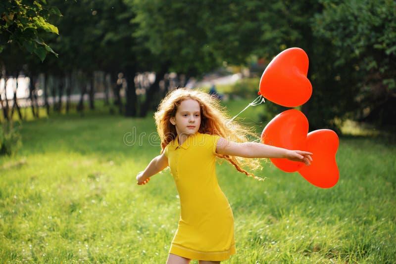 A menina bonito com coração vermelho balloons o descanso em um parque do verão foto de stock royalty free