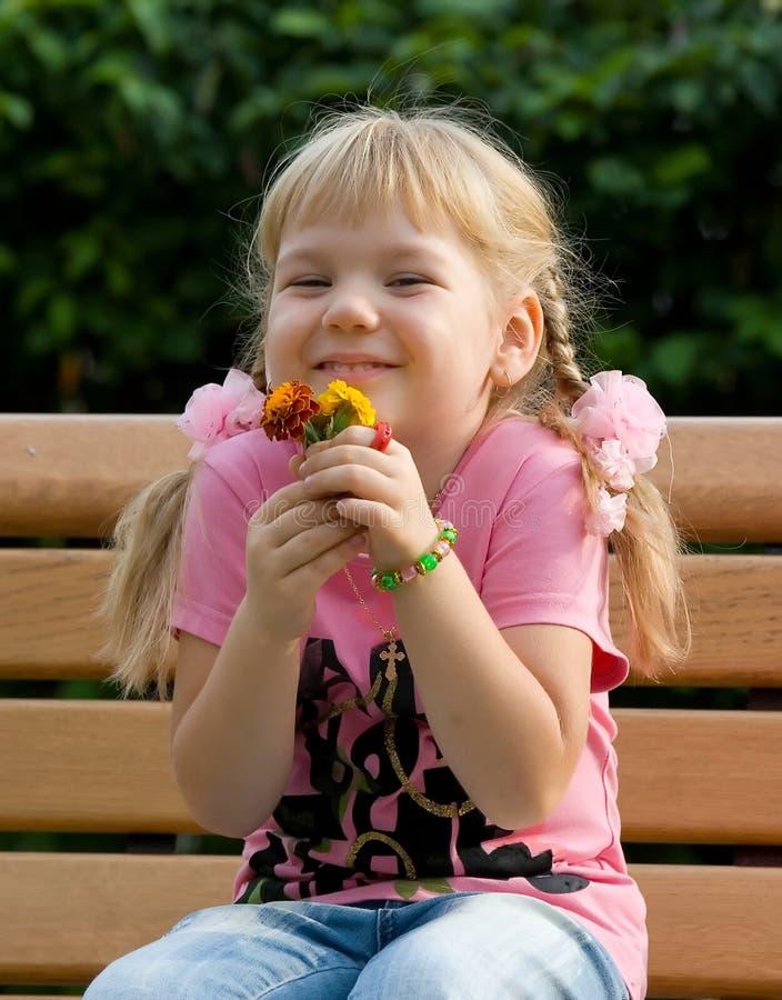 Menina bonito com flores. fotografia de stock