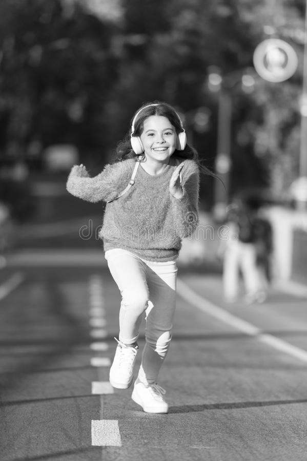 Menina bonito com fones de ouvido Pouca crian?a para apreciar a atividade Corredor de passeio da crian?a na m?sica de escuta do p imagem de stock royalty free