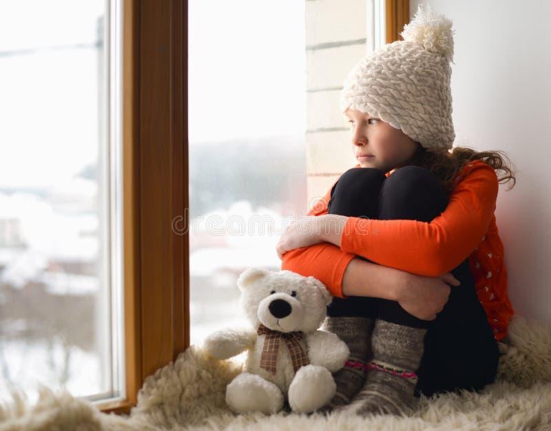 Menina bonito com a janela próxima sozinha de assento do cabelo longo em uma soleira foto de stock royalty free