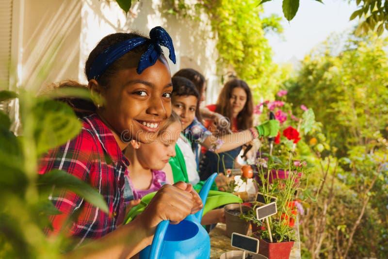 Menina bonito com a lata molhando que trabalha no jardim imagens de stock royalty free