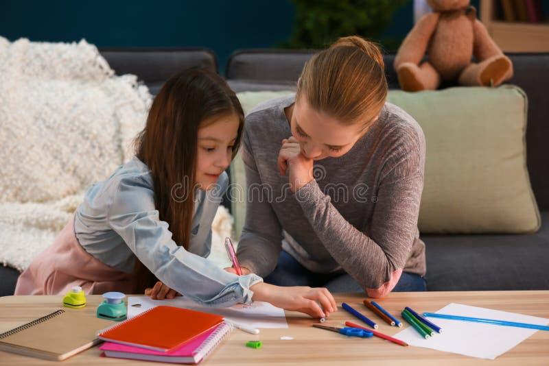 Menina bonito com a mãe que faz trabalhos de casa em casa imagens de stock