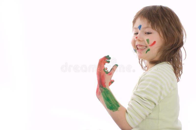 Menina bonito com mãos e a face pintadas foto de stock