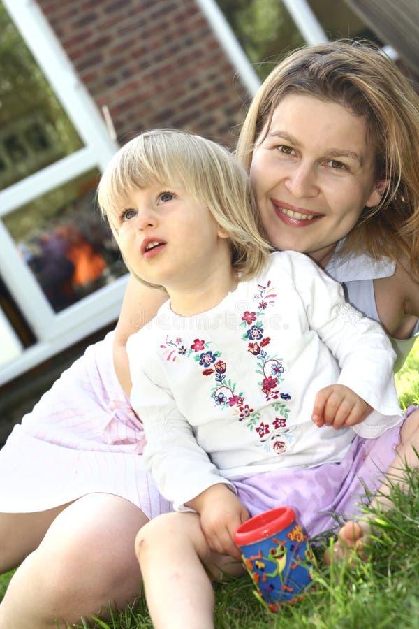 Menina bonito com a mamã no jardim imagens de stock