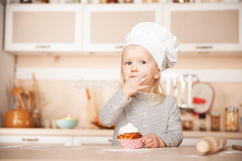 Menina bonito com o bolo do gosto do chapéu do cozinheiro chefe na cozinha fotos de stock royalty free