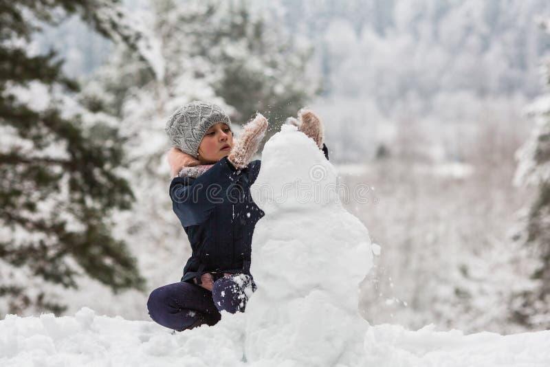 Menina bonito com o boneco de neve no parque do inverno foto de stock
