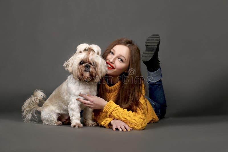 Menina bonito com o cão adorável de Shih-tzu no fundo escuro foto de stock royalty free