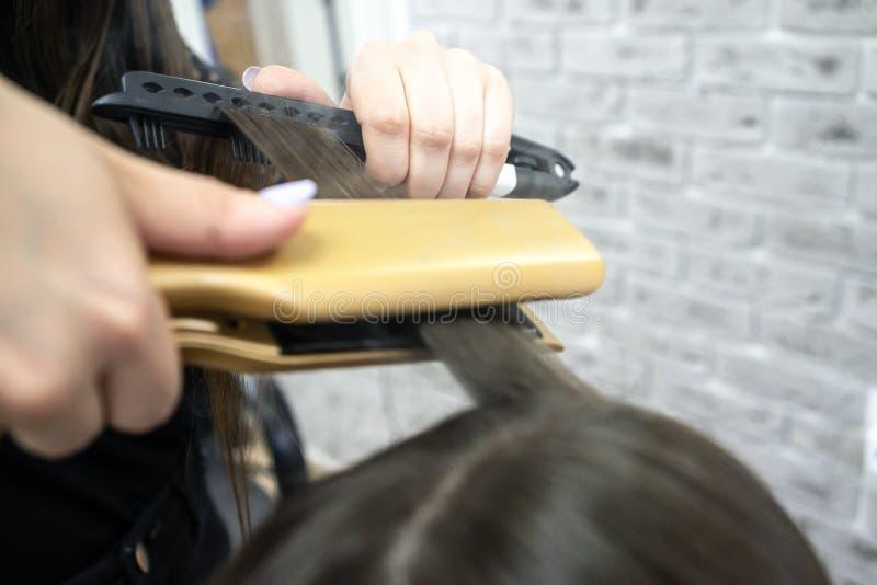 Menina bonito com o cabeleireiro moreno longo do cabelo que faz a laminação do cabelo em um salão de beleza conceito do tratament foto de stock
