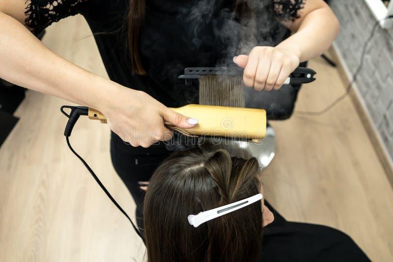 Menina bonito com o cabeleireiro moreno longo do cabelo que faz a laminação do cabelo em um salão de beleza conceito do tratament imagem de stock