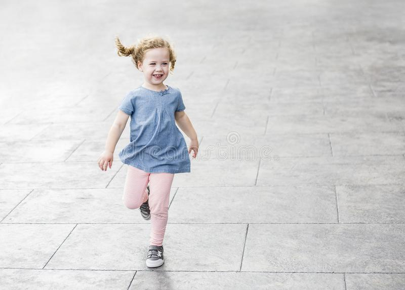 Menina bonito com o cabelo encaracolado que corre e que ri fora Copie o espaço fotografia de stock