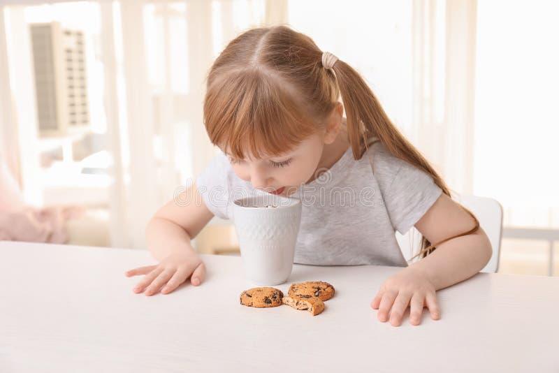Menina bonito com o copo da bebida e de cookies quentes do cacau em casa fotos de stock royalty free