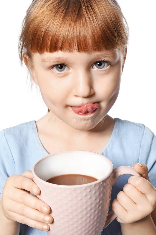 Menina bonito com o copo da bebida quente do cacau no fundo branco imagens de stock
