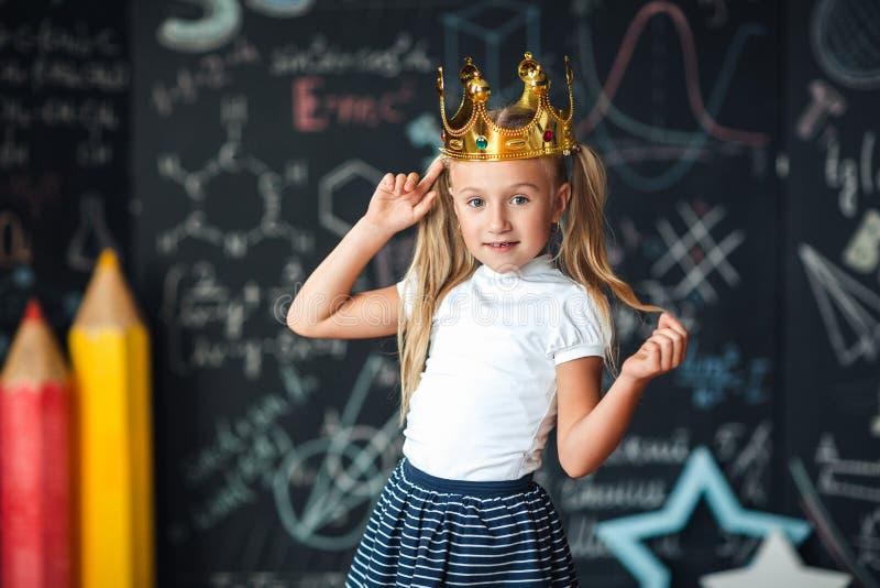 Menina bonito com o desenho da coroa da princesa acima da cabeça que estuda na sala de aula foto de stock