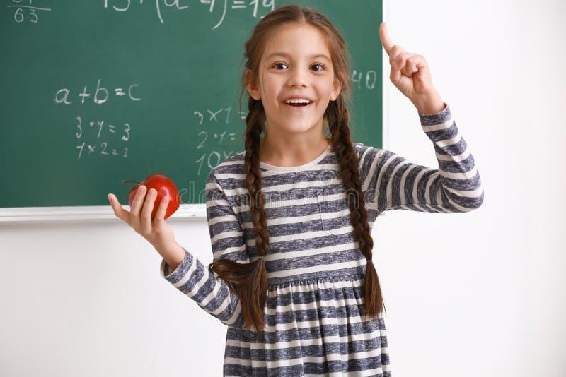 Menina bonito com o indicador aumentado na sala de aula imagem de stock royalty free