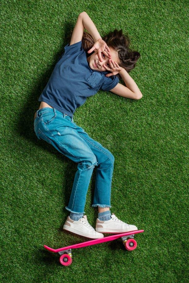 Menina bonito com o skate cor-de-rosa que encontra-se no gramado verde imagens de stock royalty free
