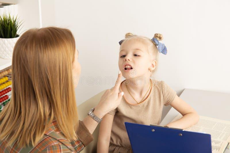 Menina bonito com o terapeuta de discurso na pronuncia??o trainiing do arm?rio imagem de stock