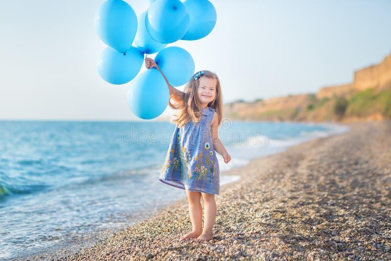 Menina bonito com os balões que levantam na praia da costa de mar do oceano com terra rochosa arenosa, um feriado, uma viagem do  fotografia de stock