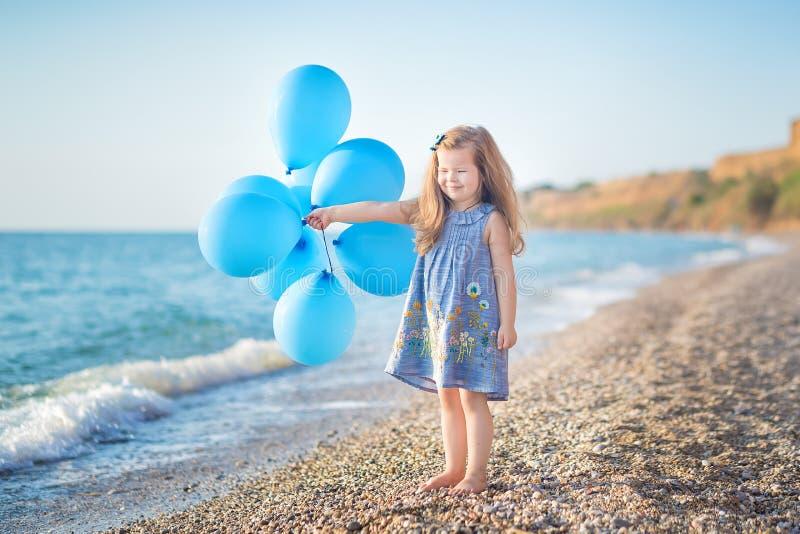 Menina bonito com os balões que levantam na praia da costa de mar do oceano com terra rochosa arenosa, um feriado, uma viagem do  imagem de stock