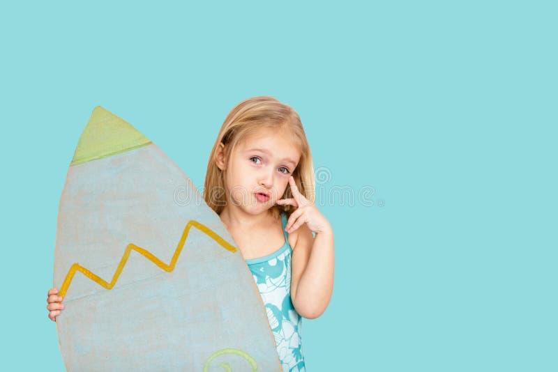 Menina bonito com a prancha da terra arrendada do cabelo louro no fundo azul Lugar para o texto fotos de stock