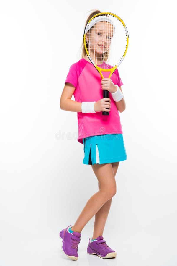 Menina bonito com a raquete de tênis na frente de sua cabeça no fundo branco imagens de stock