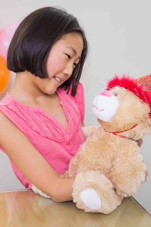 Menina bonito com seu brinquedo macio em uma festa de anos imagens de stock