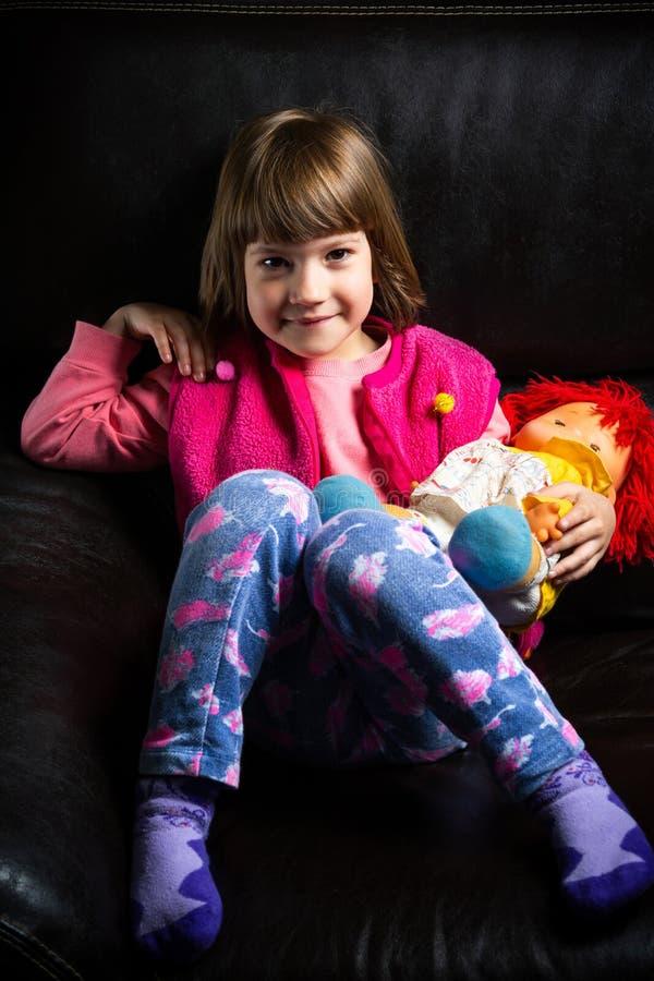 Menina bonito com seu brinquedo no sofá fotos de stock