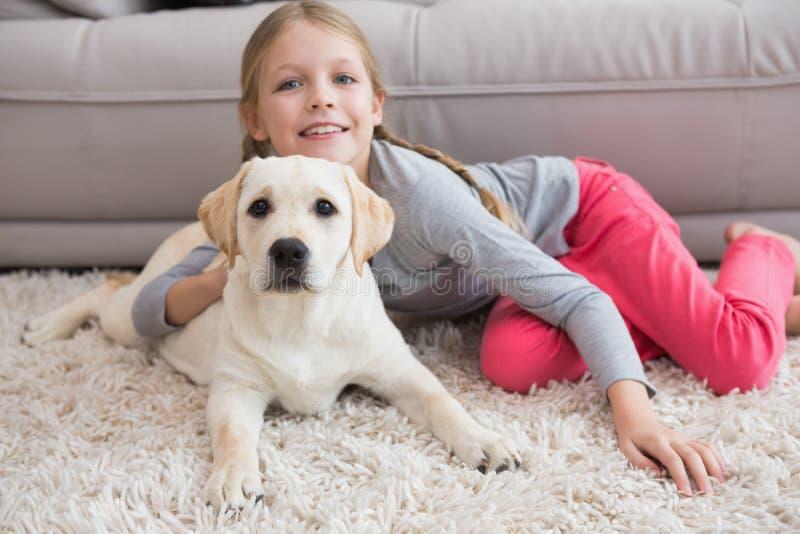 Menina bonito com seu cachorrinho no sofá imagens de stock